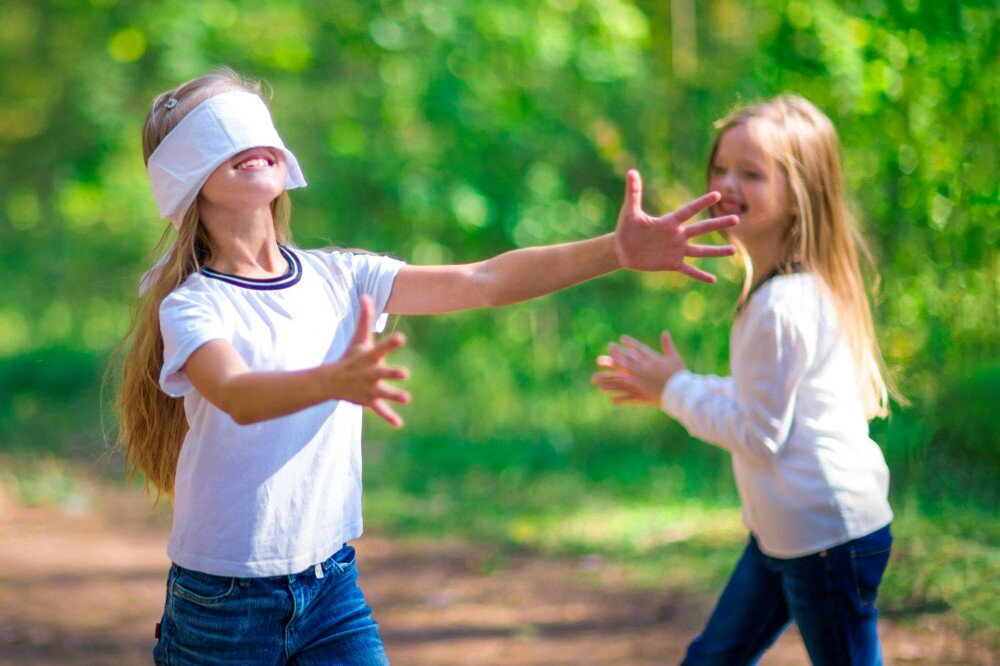 Funny girls play blind man's buff outdoors in the forest.