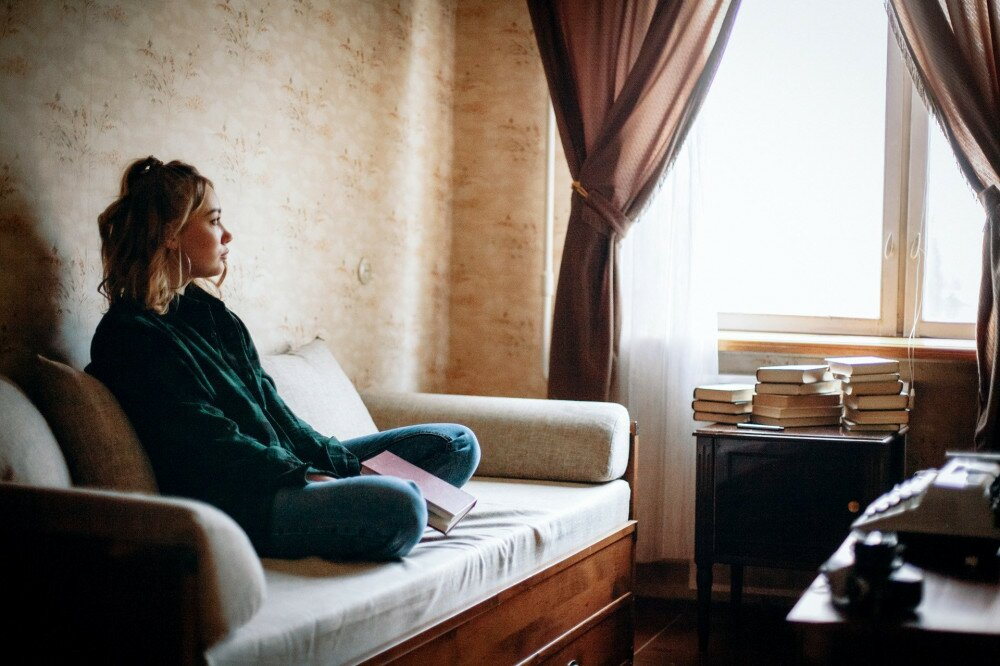 Young sad woman holding book looking through window while sitting on sofa in living room at home